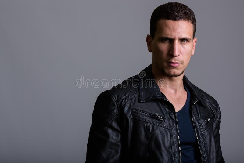 Studio shot of young muscular Persian man wearing leather jacket royalty free stock images