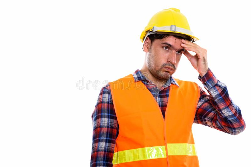 Studio shot of young Persian man construction worker looking str stock image