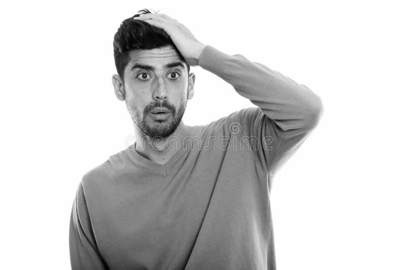 Studio shot of young Persian man looking shocked with hand on head royalty free stock image
