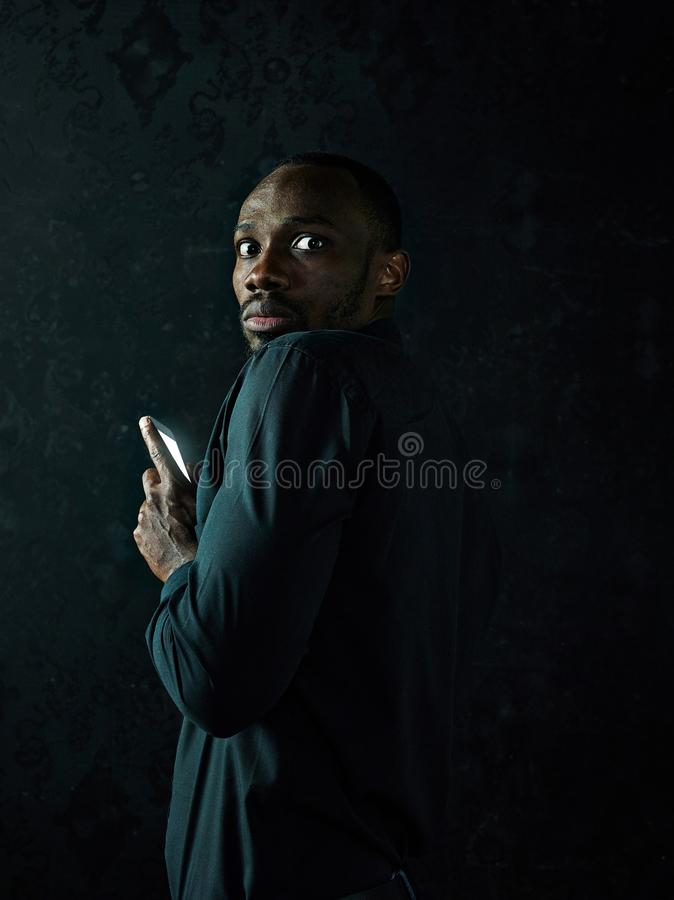 Studio shot of young serious black African man thinking while talking on mobile phone against black background royalty free stock photos