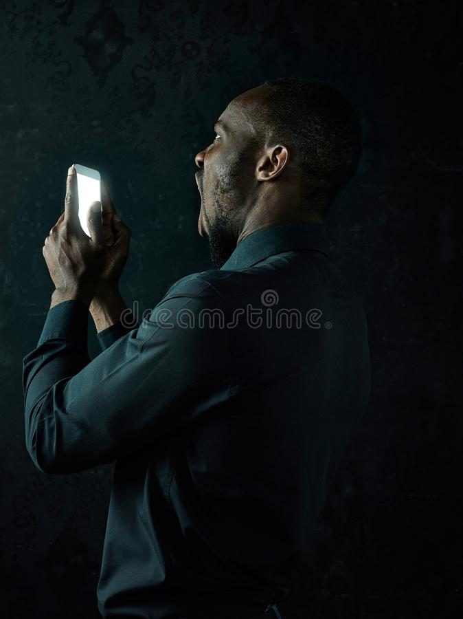 Studio shot of young serious black African man thinking while talking on mobile phone against black background stock photo