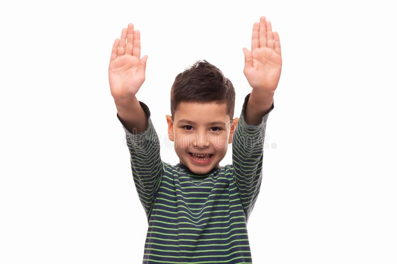 Studio shot of a young smiling boy wearing green striped shirt  standing with his hands raised, isolated with copy space royalty free stock images
