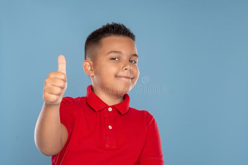 Studio shot of a young boy  civing you an approving gesture, isolated on blue  with copy space stock photography
