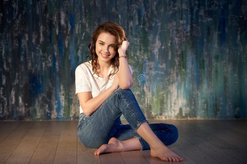 Studio shot of a young smiling girl in jeans and a t-shirt sitting on the floor. Bright sunlight, positive emotions stock photos