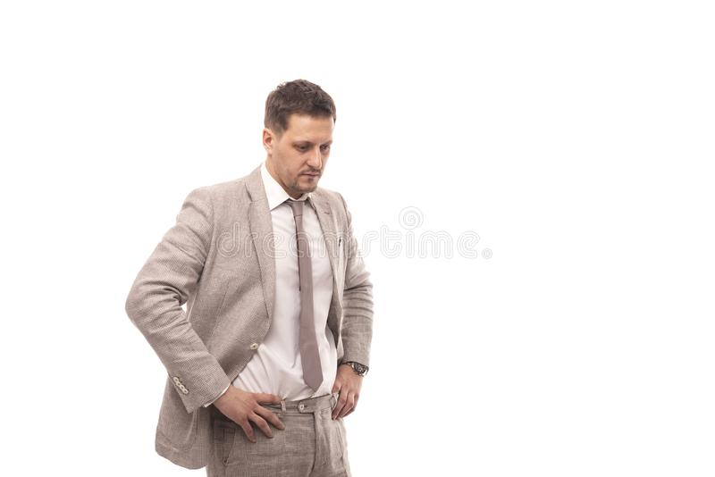 Studio shot of a young successful businessman wearing beige suit thinking about something serious , isolated royalty free stock image