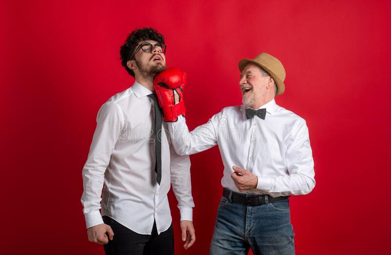 Studio shot of young versus old generation, a father and son with boxing glove. royalty free stock image