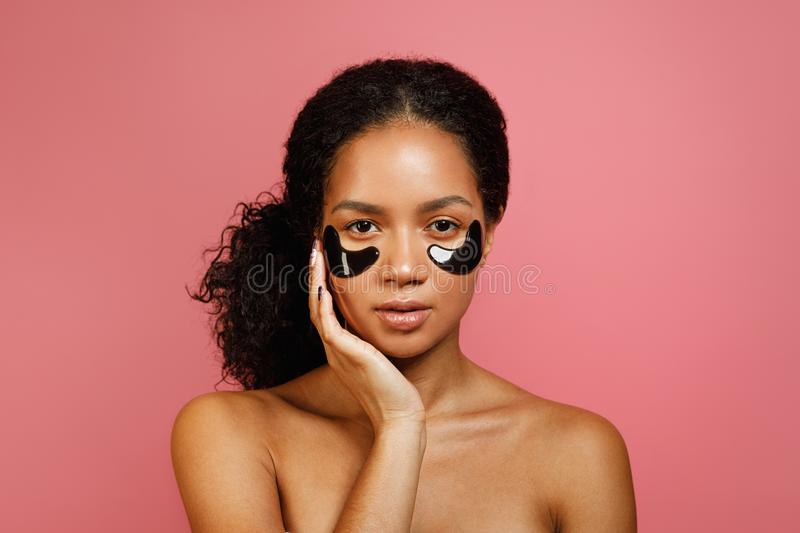 Studio shot of young woman with eye gel pads royalty free stock photos