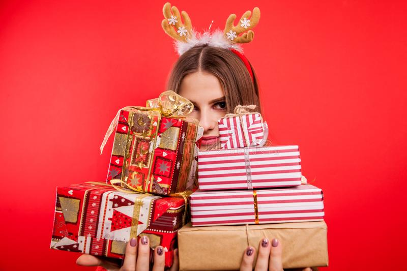 Studio shot of a young woman holding gift boxes. Christmas or New Year celebration concept. stock photography