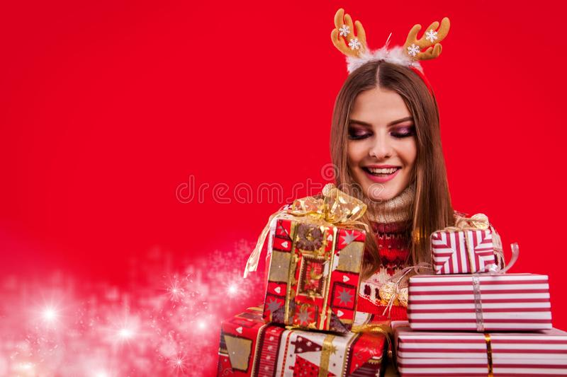 Studio shot of a young woman in Icelandic sweater holding gift boxes. Christmas or New Year celebration concept. royalty free stock photography