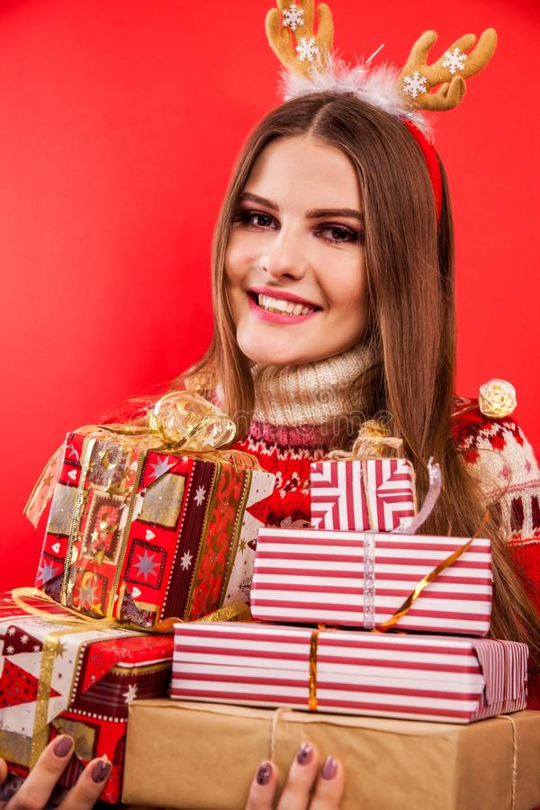 Studio shot of a young woman in Icelandic sweater holding gift boxes. Christmas or New Year celebration concept. stock photo