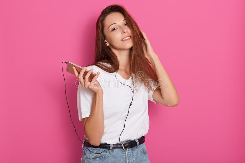 Studio shot of young woman listening to music with earphones, holding smartphone in hands, looking at camera, ralaxing at home, stock photos