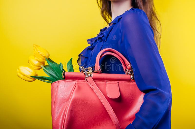 Studio shot of a young woman wearing spring outfit and holding a bag with yellow tulips royalty free stock photography