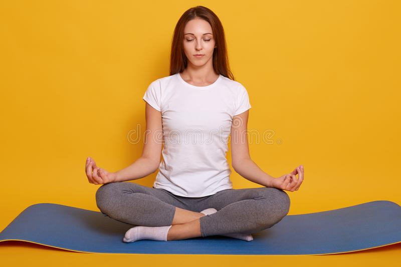 Studio shot of young woman wearing white t shirt and gray leggins, sitting on floor in lotus pose, girl holds hands in praying stock photography