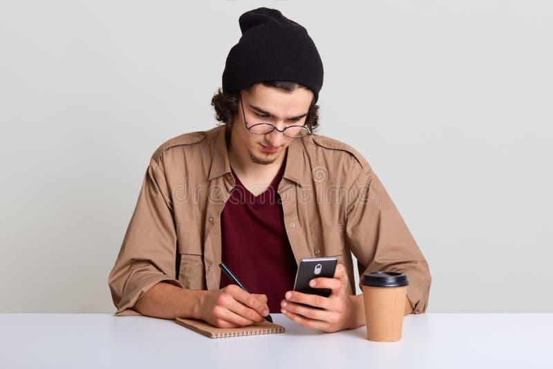 Studio sparato del giovane che si siede allo scrittorio bianco e che lavora, tenente Smart Phone a disposizione ed annotante qual fotografie stock libere da diritti