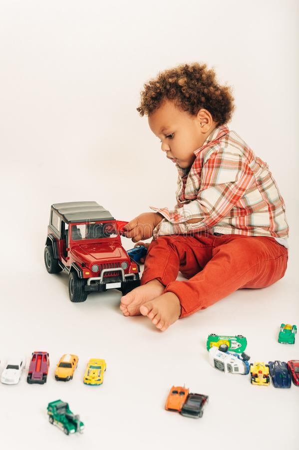 Studio sparato del neonato di 1 anno africano adorabile che gioca con le automobili variopinte immagine stock