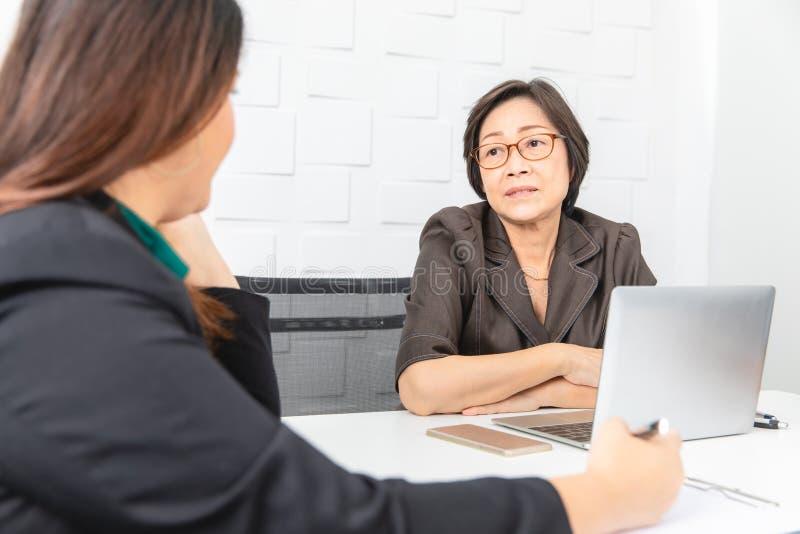 Studio sparato della donna di affari asiatica e senior con il computer portatile, sedentesi con due giovani persone nella sala ri fotografie stock