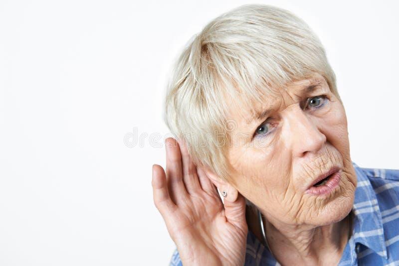 Studio sparato della donna senior che soffre dalla sordità fotografia stock libera da diritti