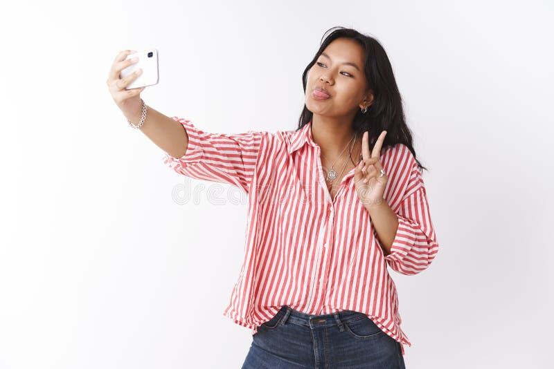 Studio sparato di bella giovane donna alla moda ed uscente sicura in blusa a strisce che imita e che fa i fronti divertenti sopra immagini stock