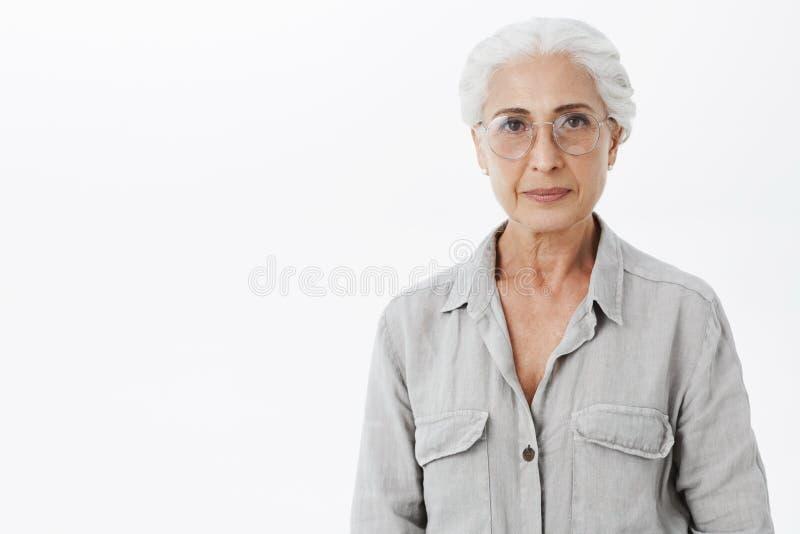 Studio sparato di doctotr femminile senior abile saggio ed intelligente in vetri con capelli grigi che stanno calmi e sicuri immagini stock
