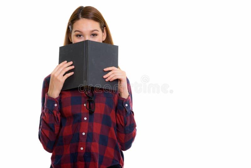 Studio sparato di giovane bella donna asiatica che si nasconde dietro il libro fotografia stock