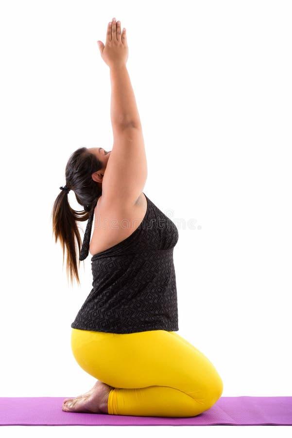 Studio sparato di giovane seduta asiatica grassa della donna mentre facendo yoga po immagini stock libere da diritti