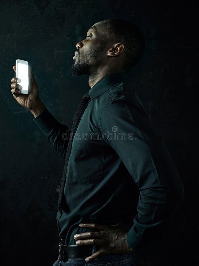 Studio sparato di giovane uomo serio dell'africano nero che pensa mentre parlando sul telefono cellulare contro il fondo nero fotografie stock libere da diritti