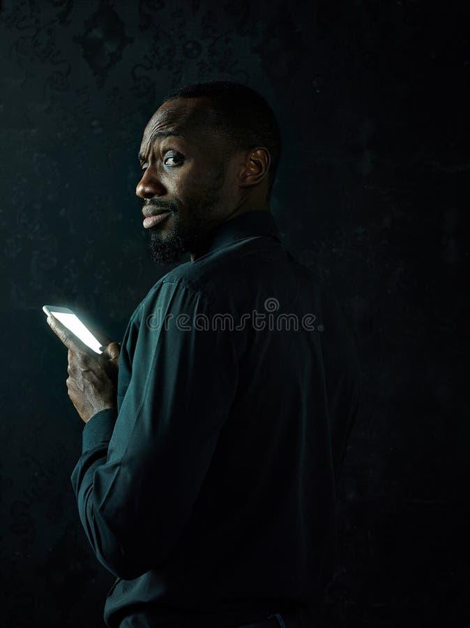 Studio sparato di giovane uomo serio dell'africano nero che pensa mentre parlando sul telefono cellulare contro il fondo nero fotografia stock
