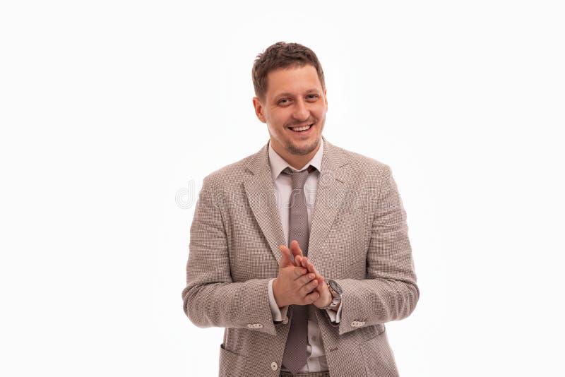 Studio sparato di giovane uomo sorridente che indossa vestito beige contro un fondo bianco fotografie stock libere da diritti