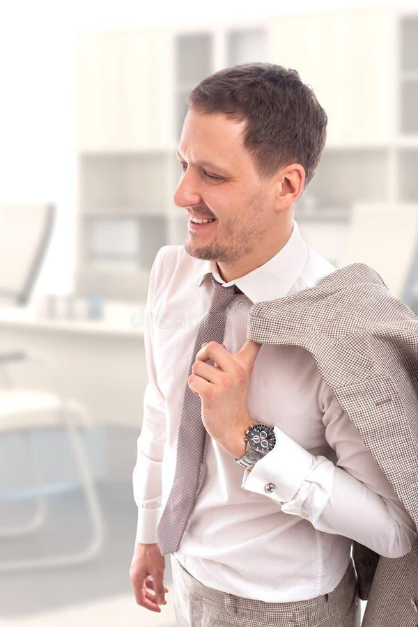 Studio sparato di giovani camicia e legame d'uso sorridenti del awhite dell'uomo d'affari maschio che giudicano un rivestimento b immagini stock libere da diritti