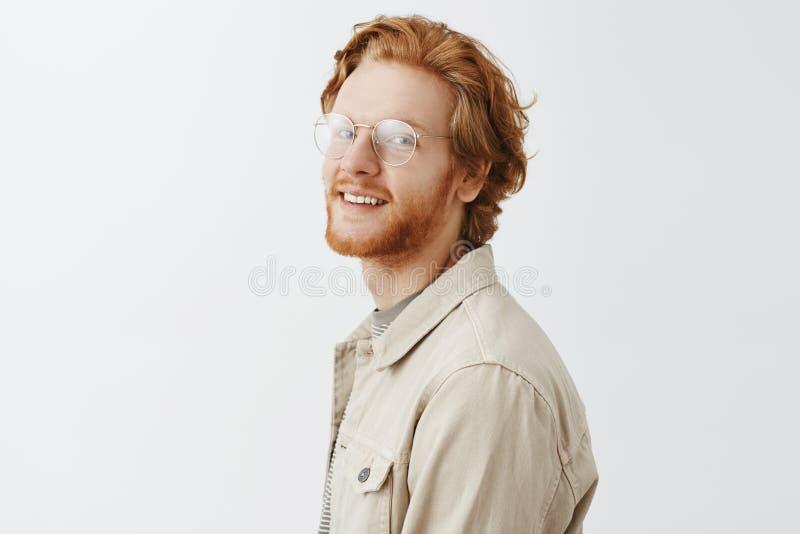 Studio sparato di incantare il tipo emotivo ed alla moda della testarossa con la barba in vetri trasparenti che stanno nel profil fotografie stock