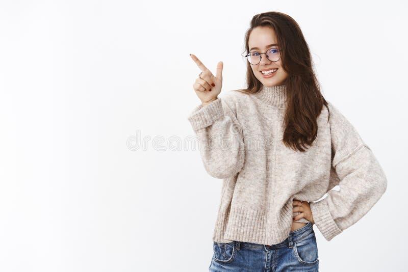 Studio sparato di incantare ragazza astuta e sicura che opera scelta, indicando all'angolo in alto a sinistra per indicare prodot fotografie stock