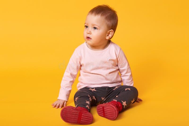 Studio sparato di piccola neonata adorabile che si siede sul pavimento, isolato su fondo giallo, uso adorabile del ritratto del b immagini stock