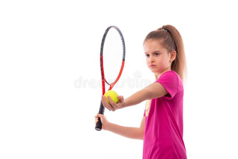 Studio sparato di piccola ragazza seria che porta maglietta rosa su un fondo bianco Sta con una racchetta e una palla di tennis e fotografie stock