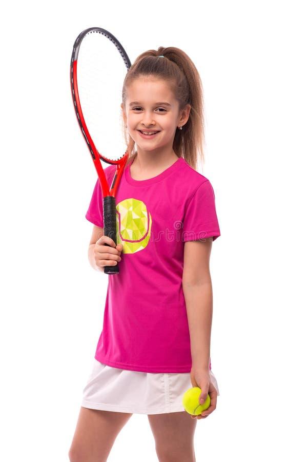 Studio sparato di piccola ragazza sorridente vestita in maglietta rosa e gonna bianca - abiti sportivi per tennis su un fondo bia immagini stock libere da diritti