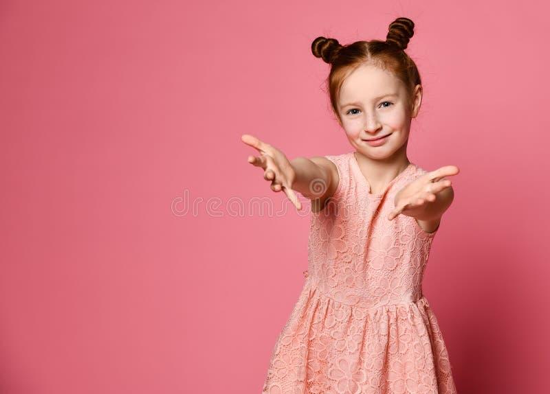 Studio sparato di una bambina sveglia amichevole della testarossa che tira le mani verso fotografie stock libere da diritti