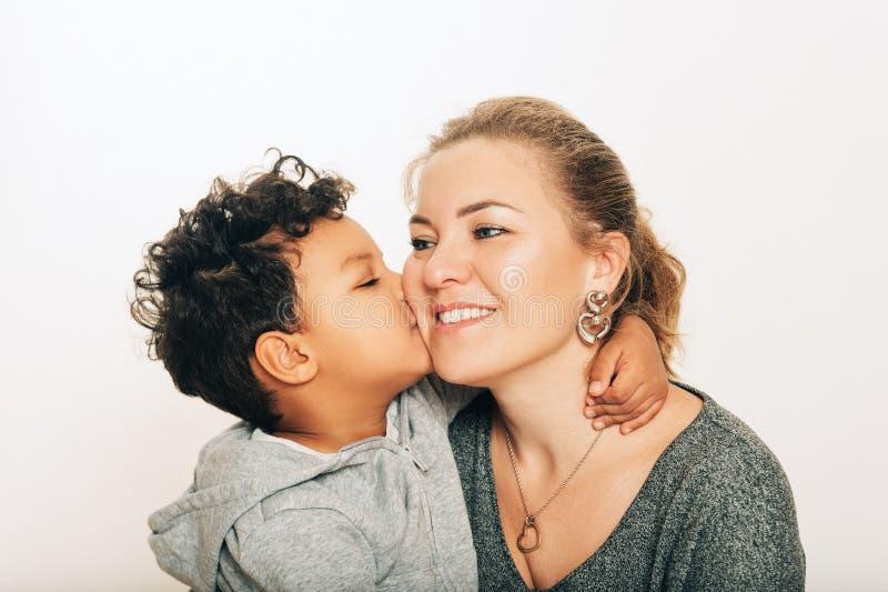 Studio strzał urocza berbeć chłopiec daje buziakowi jego matka zdjęcie royalty free