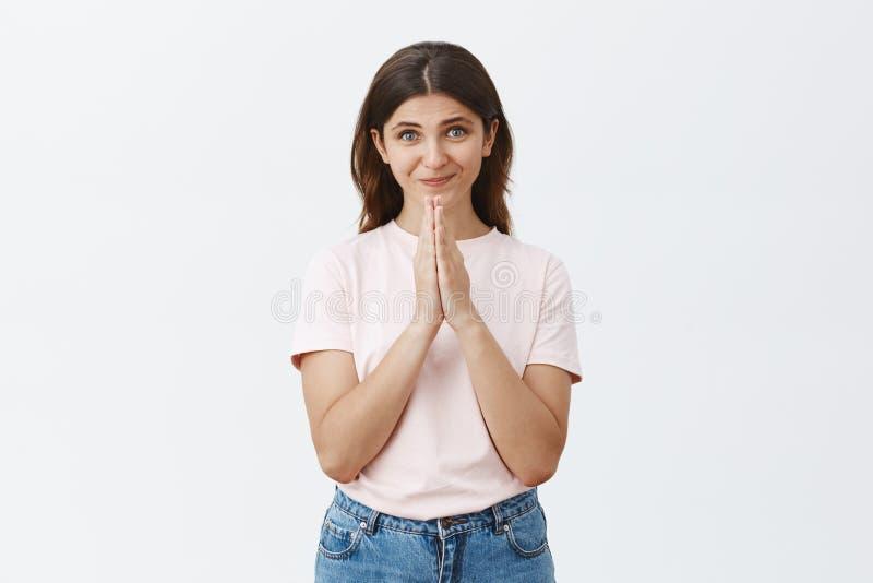 Studio strzał śliczna kobieca kobieta jest wdzięcznymi i pełny nadziei mień rękami wewnątrz modli się ono uśmiecha się delikatnie zdjęcie stock