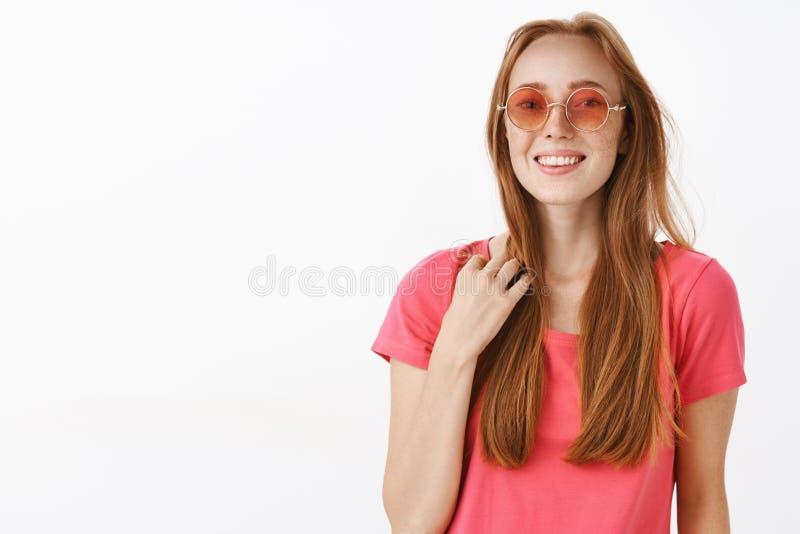 Studio strzał śliczna młoda rudzielec kobieta w różowych okularach przeciwsłonecznych i koszulki macania pasemko włosy szczęśliwa obraz stock