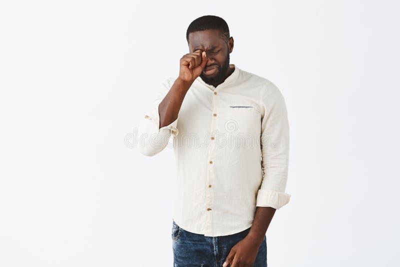 Studio strzał atrakcyjny bojaźliwy i niepewny dorosły amerykanina afrykańskiego pochodzenia mężczyzna z brodą w białej koszula pł obraz stock