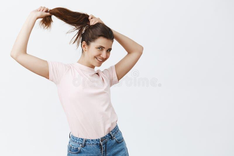 Studio strzał beztroskiego i budzący emocje ślicznego europejskiego dziewczyny czesania długa brown włosiana robi fryzura podczas obraz stock