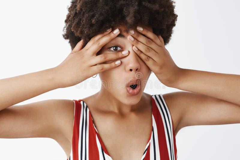 Studio strza? ciekawy atrakcyjny ciemnosk?ry kobieta model z afro fryzur? w pasiastym odzie?owym nakryciu ono przygl?da si? z zdjęcie royalty free