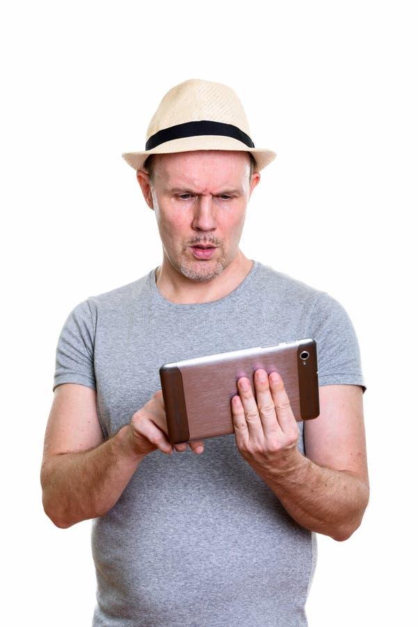 Studio strzał dojrzały mężczyzna używa cyfrową pastylkę patrzeje wprawiać w zakłopotanie zdjęcie royalty free