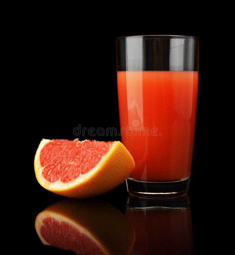 Studio strzał grapefruitowy sok i ćwiartka odizolowywający na czerni fotografia stock