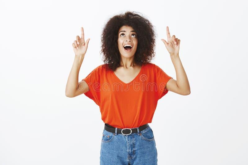 Studio strzał imponująca zadowolona atrakcyjna afroamerykańska kobieta z afro fryzurą w modnym stroju, patrzeje i fotografia stock