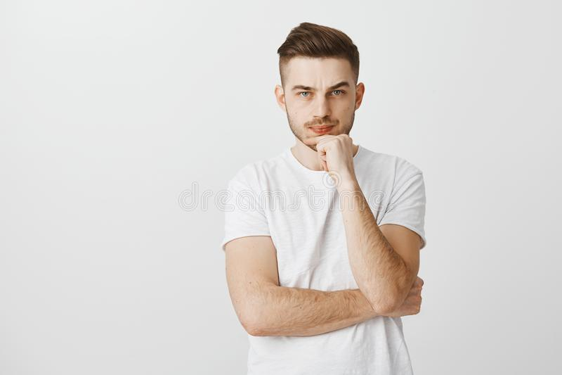 Studio strzał intensywny niepewny elegancki samiec model z chłodno fryzurą w białej koszulce marszczy brwi pouting rękę i trzymać obrazy stock