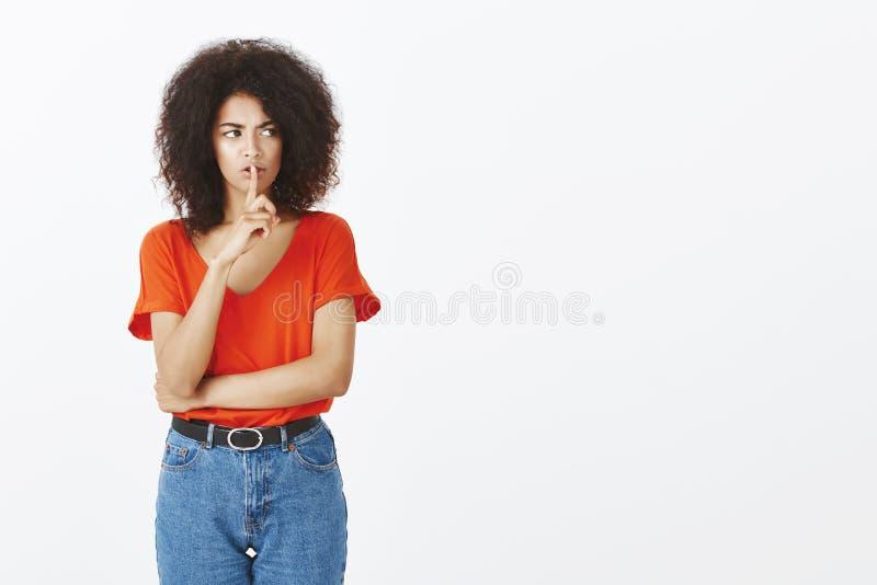 Studio strzał intensywny nieszczęśliwy ciemnoskóry kobieta model z afro fryzurą, mówić shh podczas gdy robić shush gest z fotografia stock