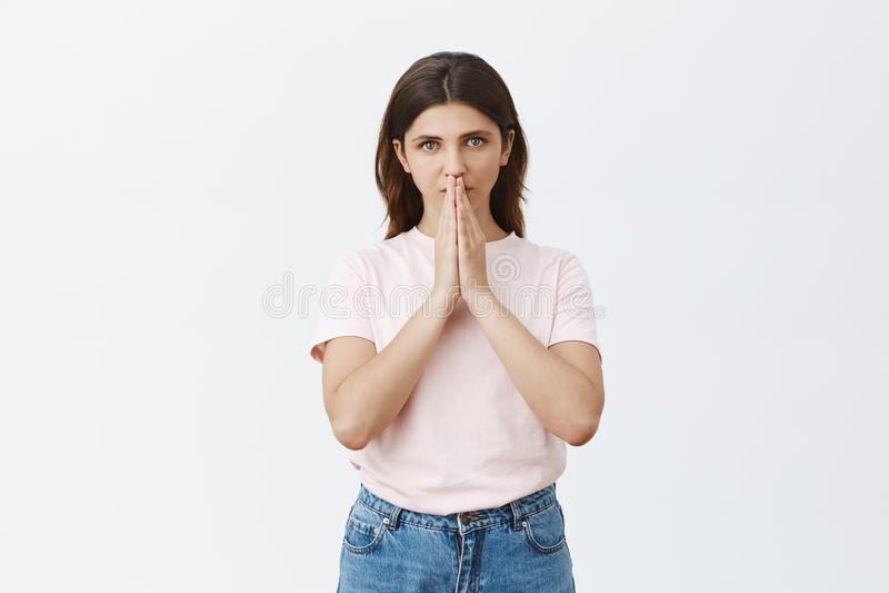 Studio strzał kobieta ma wiarę w bóg mienia rękach wewnątrz ono modli się blisko usta i gapić się przy kamery modleniem poważnego fotografia stock