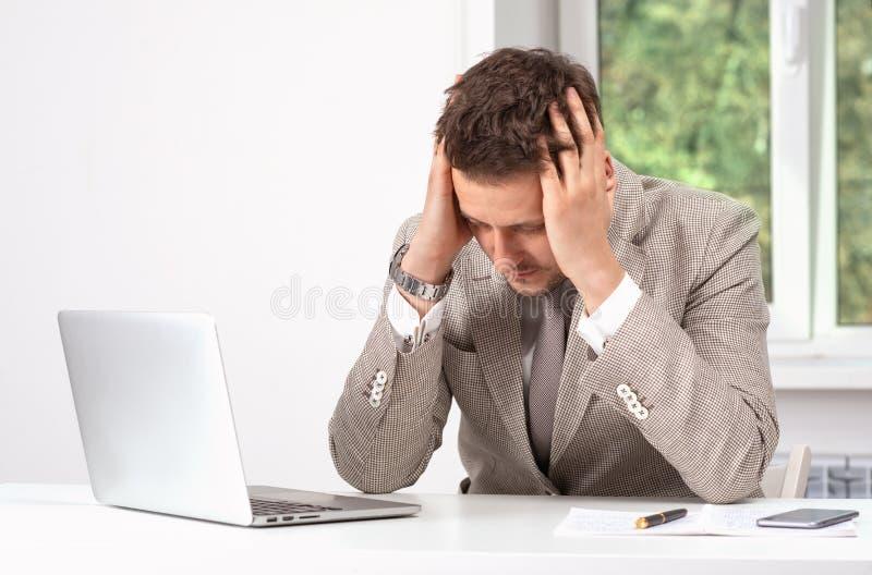 Studio strzał mężczyzna jest ubranym beżową kurtkę i krawat pracuje na laptopie Jest wzburzony o coś, spinający jego głowę z obraz royalty free