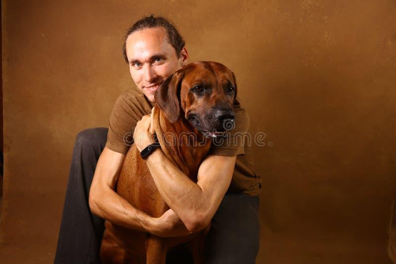 Studio strzał mężczyzna z Rhodesian Ridgeback psem na brązu tle fotografia stock