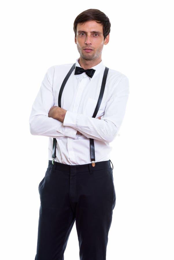 Studio strzał młoda przystojna mężczyzna pozycja podczas gdy będący ubranym zawiesza obrazy stock